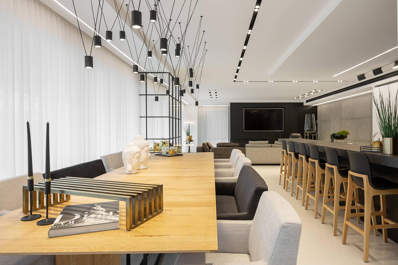 גופי תאורה תלויים שחורים מעוצבים מעל שולחן אוכל